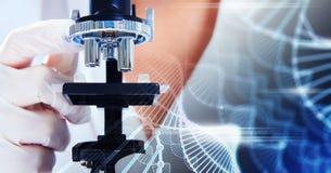 Wetenschapper die door een microscoopclose-up kijken Stock Foto's