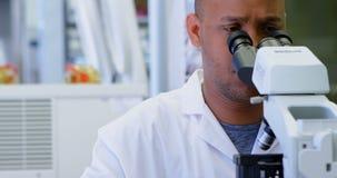 Wetenschapper die door microscoop 4k kijken stock footage