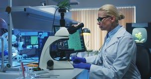 Wetenschapper die een microscoop in een laboratorium gebruiken stock video