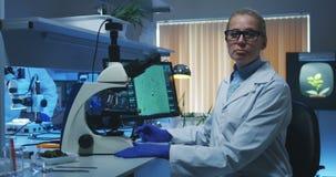 Wetenschapper die een microscoop in een laboratorium gebruiken stock videobeelden