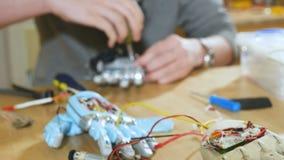 Wetenschapper die innovatief cybernetisch robotachtig wapen assembleren Hi-tech innovatieve technologie stock video