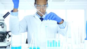 Wetenschapper die in laboratorium, het gieten chemische oplossing in reageerbuis werken stock video