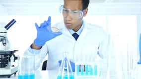Wetenschapper die in laboratorium reactie in horlogeglas bestuderen stock videobeelden
