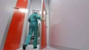 Wetenschapper die laboratoriumruimte ingaan Farmaceutische arbeider die witte gang lopen stock videobeelden