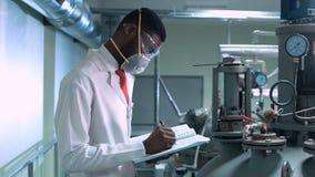 Wetenschapper die in masker in laboratorium schrijven stock video