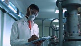 Wetenschapper die in masker in laboratorium schrijven stock videobeelden
