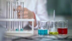 Wetenschapper die met vloeistof in laboratoriumglaswerk werken Reageerbuizen die vloeistof vullen stock footage
