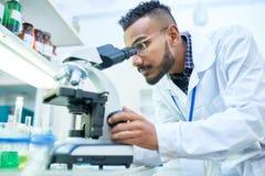 Wetenschapper die microscoop in laboratorium gebruikt stock foto