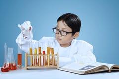 Wetenschapper die pipet voor het laten vallen van chemisch product met behulp van Royalty-vrije Stock Foto's