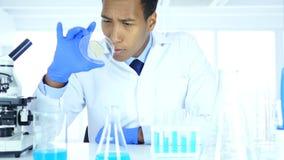 Wetenschapper die reactie in horlogeglas en microscoop in laboratorium kijken stock videobeelden