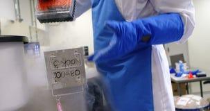 Wetenschapper die vaccinrek van diepvriezer 4k nemen stock videobeelden
