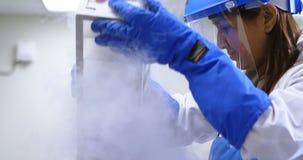 Wetenschapper die verticaal diepvriezerrek verwijderen uit diepvriezer 4k stock videobeelden