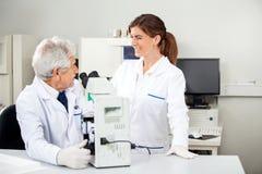 Wetenschapper Discussing With Colleague terwijl het Gebruiken Royalty-vrije Stock Foto