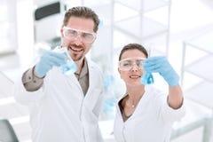 Wetenschapper en medewerker met buizen, die zich in het laboratorium bevinden royalty-vrije stock fotografie