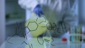 Wetenschapper gietende biofuel in laboratoriumfles, chemische formule op glasraad stock video