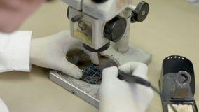 Wetenschapper in het laboratorium die een microscoop en een soldeersel onderzoeken stock video