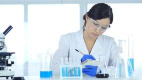 Wetenschapper het schrijven details, resultaat van onderzoek naar laboratorium stock foto