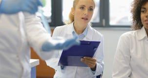 Wetenschapper Hold Test Tube terwijl de Groep van het Mengelingsras Onderzoekers die Nota's van Experiment in Modern Laboratorium stock footage