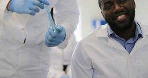 Wetenschapper Hold Test Tube terwijl Groep Onderzoekers die Nota's van Experiment in Modern Laboratorium maken stock footage