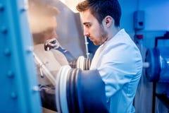 Wetenschapper met beschermende rovershandschoenen voor de behandeling van gevaarlijke substanties in steriel milieu royalty-vrije stock foto