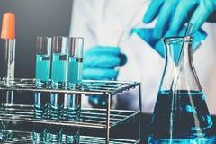 Wetenschapper met de hulpmiddelen van de materiaalholding tijdens het wetenschappelijke concept van de experimentwetenschap stock afbeelding