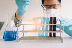 Wetenschapper onderzoeken die met chemische vloeistof met het gebruiken van dro werken stock foto's