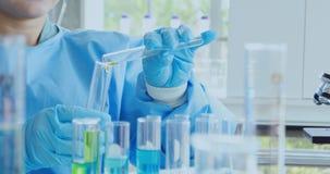 Wetenschapper Pouring Liquid in Reageerbuis stock footage