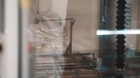 Wetenschapper in witte robe en rubberhandschoenen gezette lenzen in glasdoos stock footage