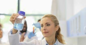 Wetenschapper Woman Analyzing Bottle met Chemische producten in Laboratorium het Gelukkige Glimlachen over het Sprekende Ras Team stock videobeelden