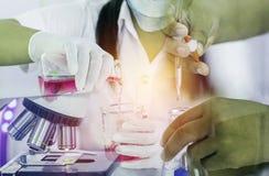 Wetenschapperhand met het laten vallen van chemische vloeistof met de chemievloeistof van het wetenschapper dragende onderzoek aa stock foto's