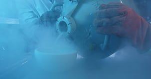 Wetenschappers die chemisch product in mortier 4k gieten stock footage