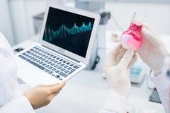 Wetenschappers die DNA van vleessteekproef bestuderen stock afbeelding