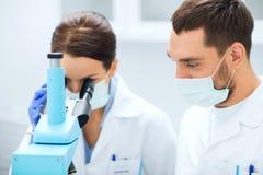 Wetenschappers die in maskers aan microscoop laboratorium bekijken Stock Foto's