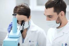 Wetenschappers die in maskers aan microscoop laboratorium bekijken Stock Afbeeldingen