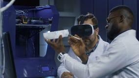 Wetenschappers die met 3d druk en VR werken stock footage