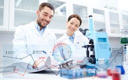 Wetenschappers die met microscoop onderzoek naar laboratorium maken royalty-vrije stock afbeeldingen