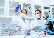 Wetenschappers die met reageerbuizen onderzoek maken bij laboratorium stock fotografie