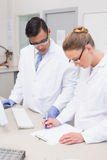 Wetenschappers die op klembord schrijven stock fotografie