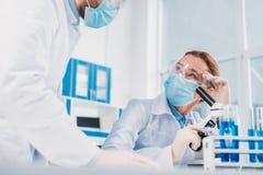 wetenschappers die in witte lagen, medische handschoenen en beschermende brillen wetenschappelijk onderzoek samen maken stock afbeelding