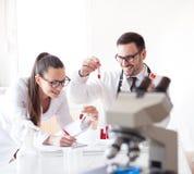 Wetenschappers in laboratorium met microscoop stock afbeeldingen