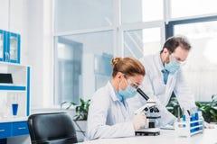 wetenschappers in medische maskers en beschermende brillen die bij het wetenschappelijke onderzoek werken stock afbeelding