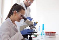 Wetenschappers met groenten in laboratorium stock foto