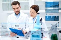 Wetenschappers met tabletpc en microscoop in laboratorium royalty-vrije stock afbeeldingen
