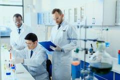 Wetenschappers in witte lagen die in chemisch laboratorium samenwerken stock afbeeldingen