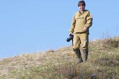 Wetenschappersfotograaf die zich bovenop een heuvel bevinden Stock Foto