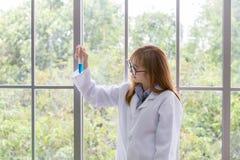 Wetenschapswhit blauwe geestmening Wetenschappelijk substantieblauw binnen op haar hand bij laboratorium een achtergrond Mooie gl stock afbeelding