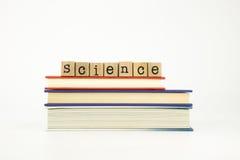 Wetenschapswoord op houten zegels en boeken stock foto's
