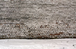 Wethered brick wall and pile of snow. Royalty Free Stock Photos