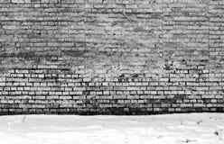 Wethered tegelstenvägg och hög av snö Arkivbild