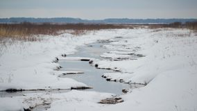 Wetland creek vanishing into the grasslands - on a snowy cold winter overcast day in the Crex Meadows Wildlife Area in Northern Wi royalty free stock image